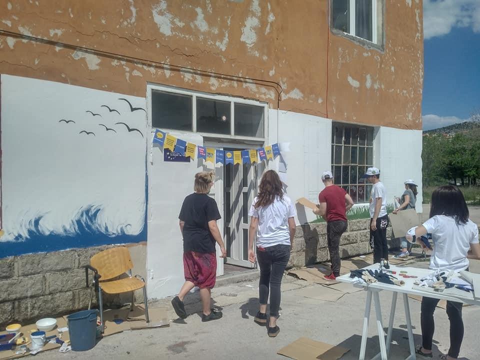 mladi oslikavaju zgradu