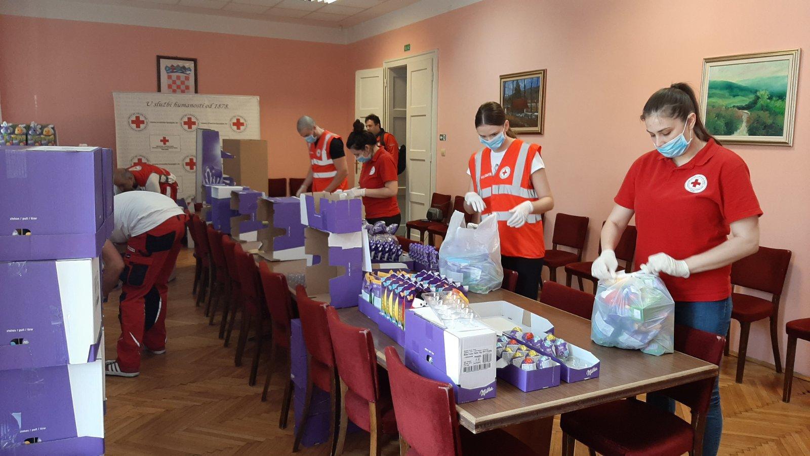 sedmero volontera slaže humanitarnu pomoć u kutije