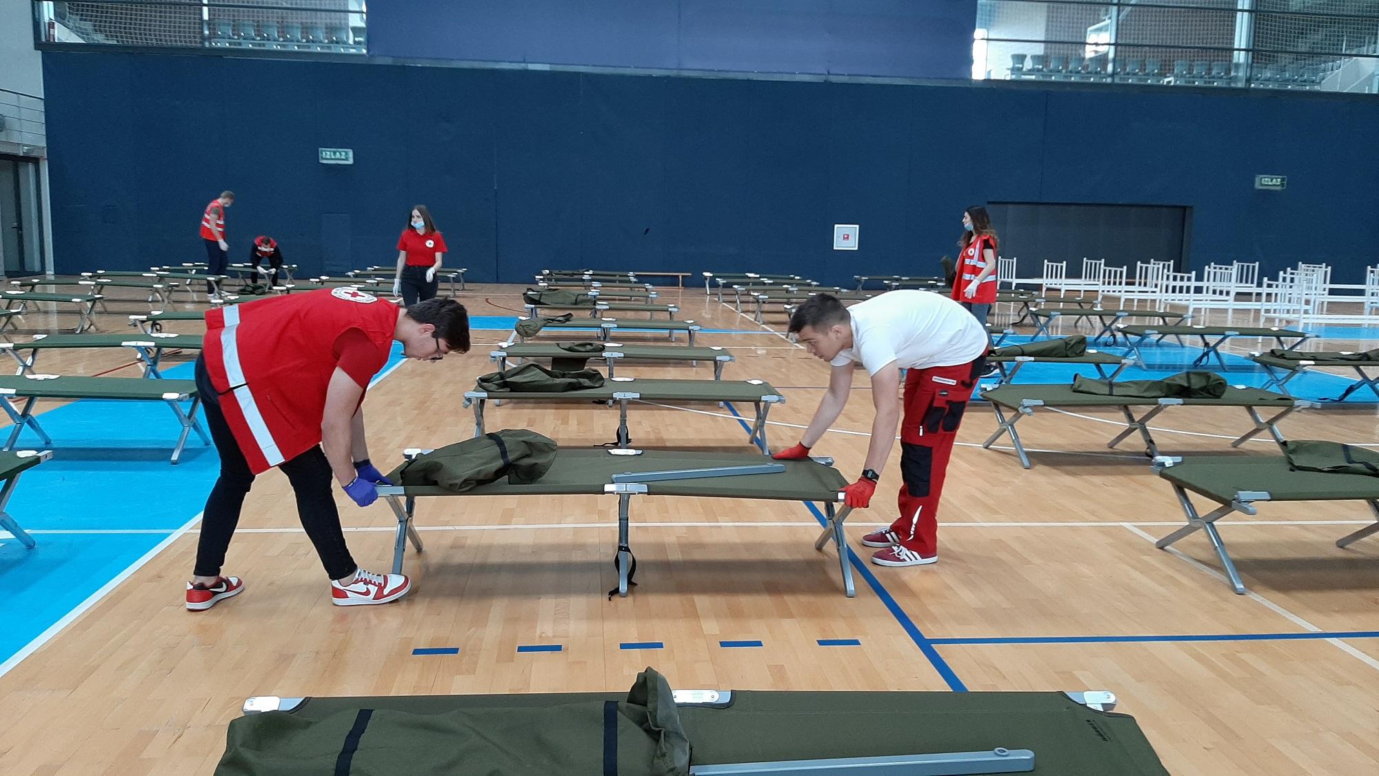 Volonteri namještaju ležajeve u sportskoj dvorani